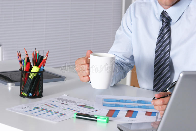 Handsome businessman having tea or coffee in office.  stock photo