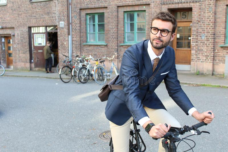 Handsome businessman heading to work by bike stock photo