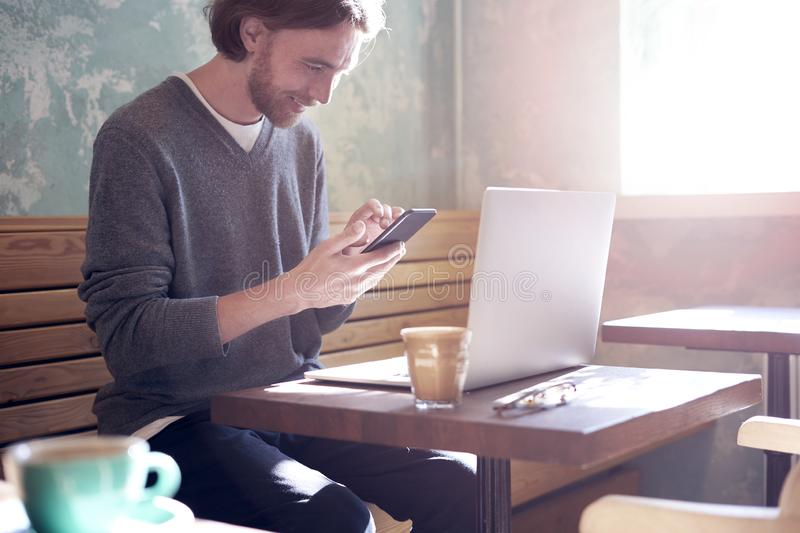 Handsome businessman hipster with long hair working on laptop in sunny cafe, calling someone by smartphone, having coffee stock photos