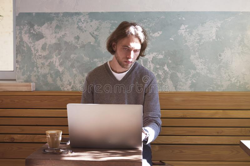 Handsome businessman hipster with long hair working on laptop in sunny cafe, having coffee in glass. Horizontal royalty free stock photo