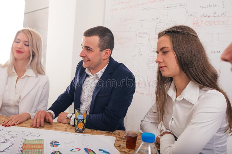 Handsome businessman with his two female architects smiling and discussing a project stock photos