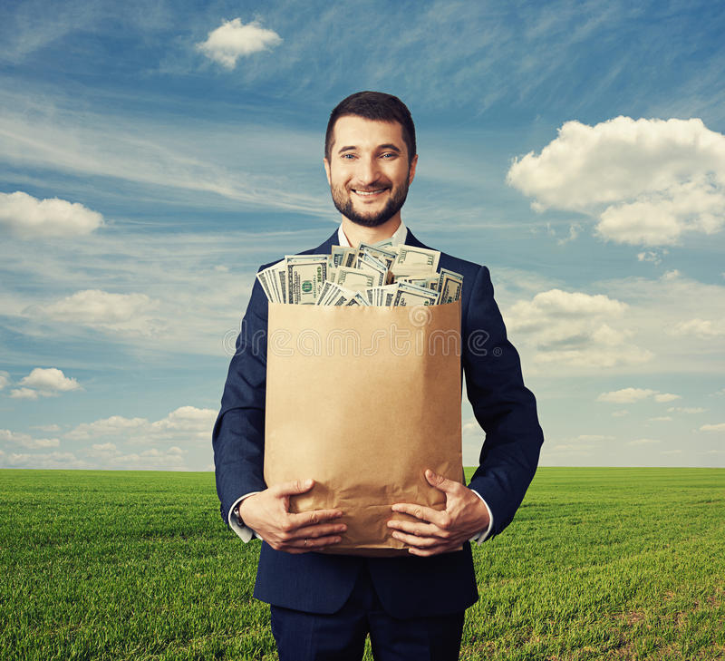 Handsome businessman holding paper bag with money stock photo