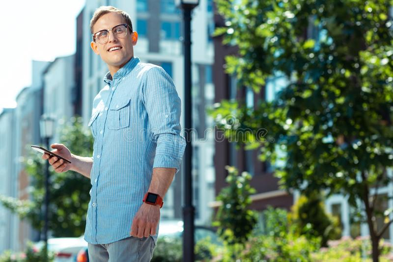 Handsome businessman holding smartphone while standing outside stock photos