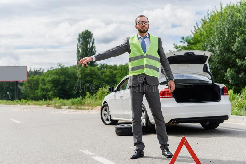 handsome businessman in light green vest stopping car stock photos