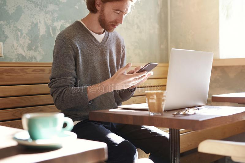 Handsome businessman with long hair wearing sweater calling by smartphone sitting in sunny cafe, using laptop having coffee alone royalty free stock images