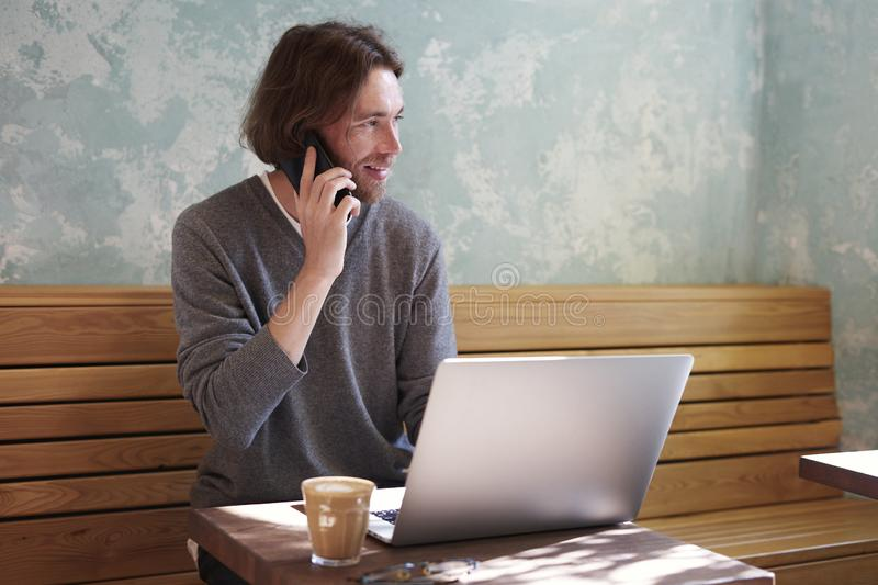 Handsome businessman with long hair wearing sweater calling by smartphone sitting in sunny cafe, using laptop having coffee alone stock photography
