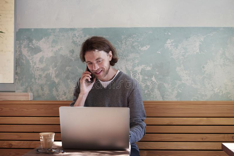 Handsome businessman with long hair wearing sweater calling by smartphone sitting in sunny cafe, using laptop having coffee alone stock image