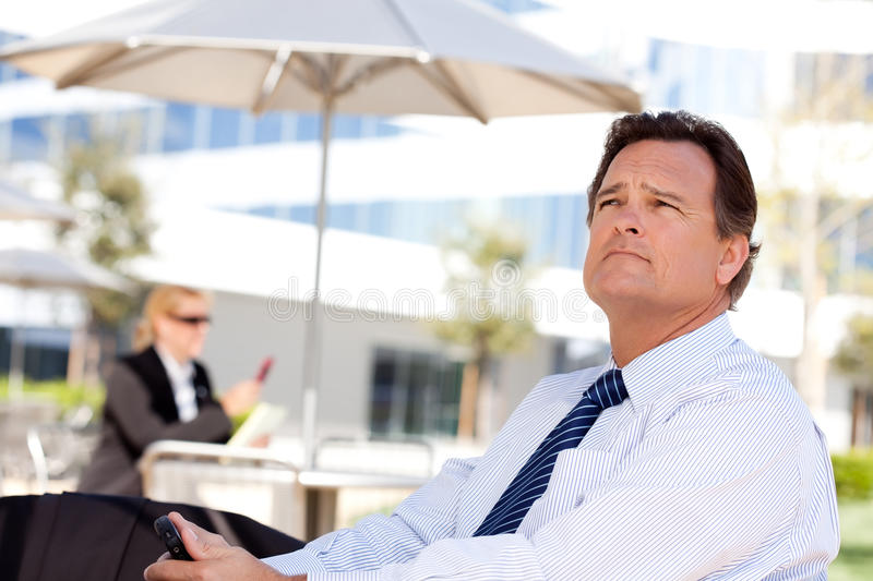 Handsome Businessman Looks Off Into the Distance. Handsome Businessman in Necktie Looks Off Into the Distance During a Break Outdoors stock photography
