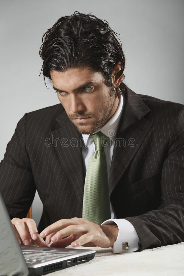 Handsome businessman looks at portable computer. With determined expression royalty free stock photo