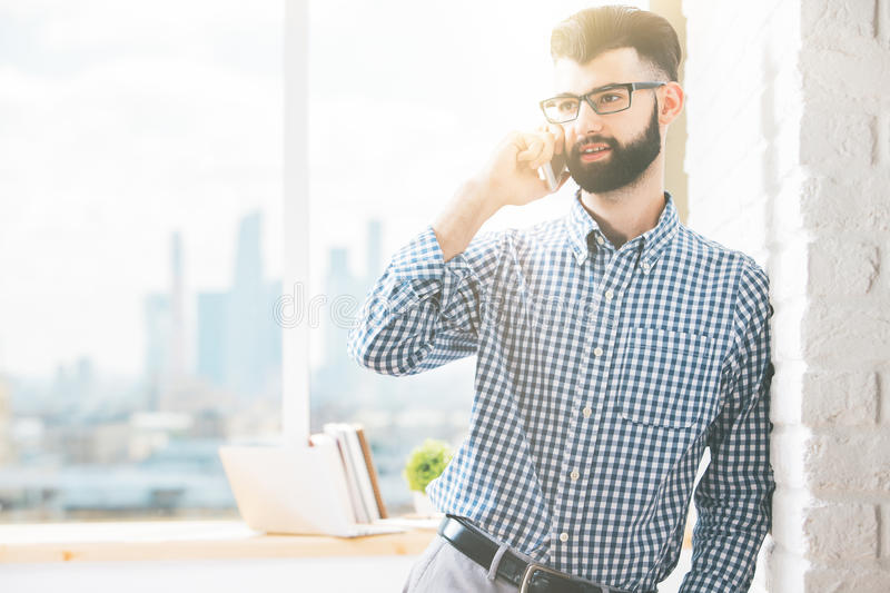 Handsome businessman on the phone. Close up portrait of cheerful handsome businessman in glasses talking on mobile phone. Communication concept royalty free stock photo