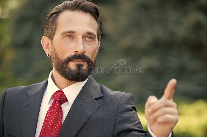 Handsome businessman point to the target in the future. Man in suit and red tie point hand forward over green outside background. stock image