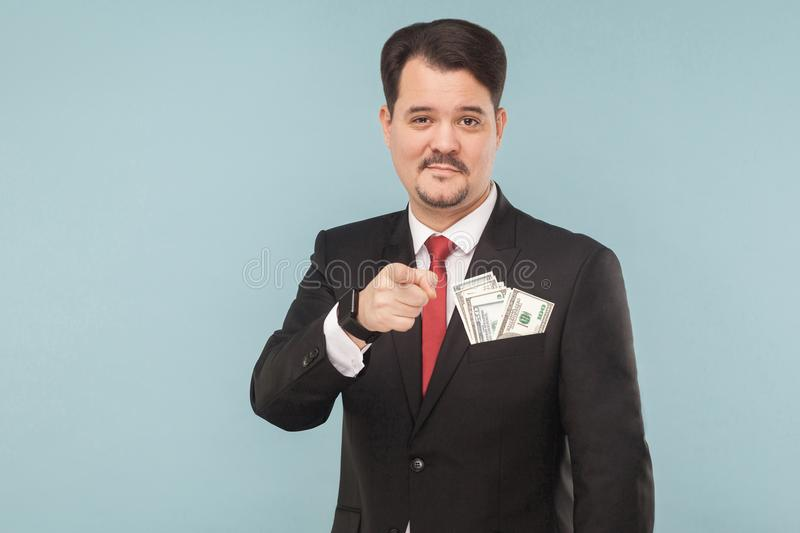 Handsome businessman pointing finger at camera with little smile stock photo