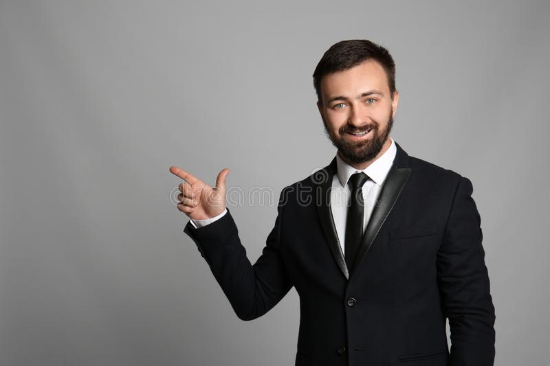 Handsome businessman pointing at something on grey background royalty free stock photos