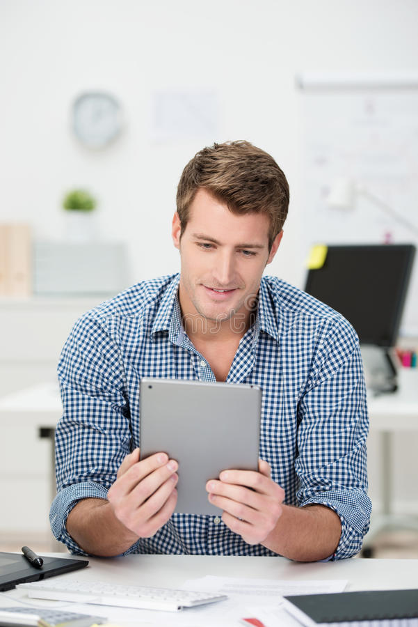 Handsome businessman reading a tablet-pc royalty free stock photography
