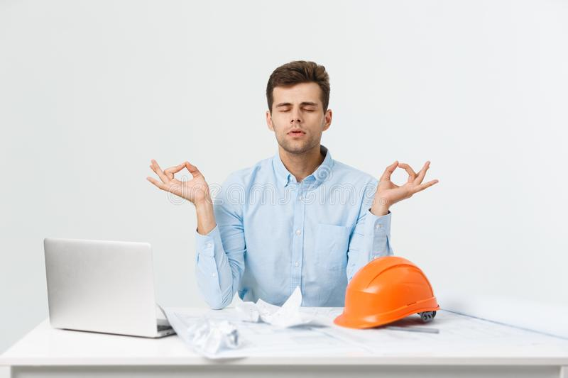 Handsome businessman is relaxing in the office, sitting in a traditional yoga lotus position. royalty free stock photos