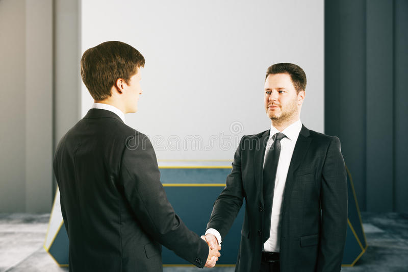 Handsome businessman shaking hands. Handsome businessmen shaking hands in office royalty free stock photography