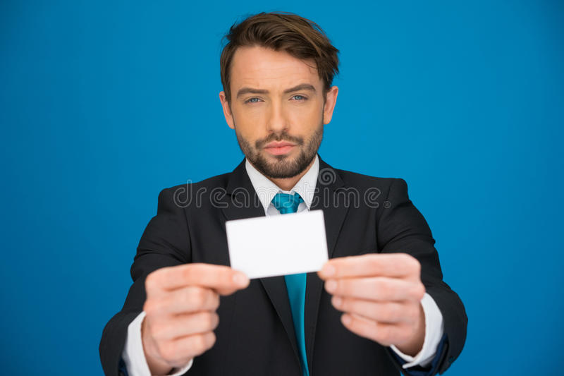 Handsome businessman showing blank business card. On blue stock photo