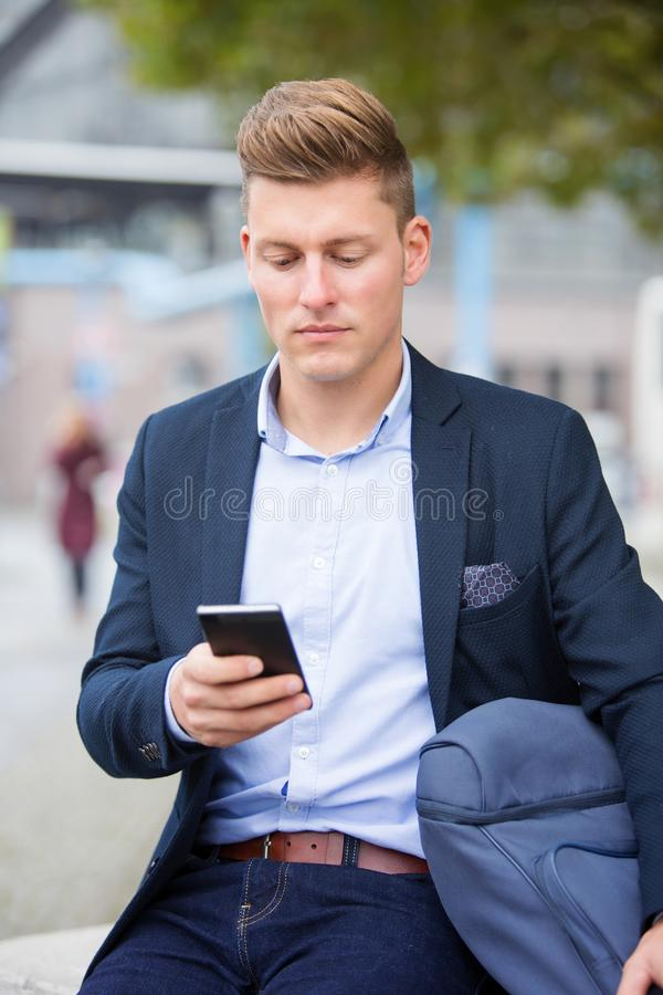 Handsome businessman sitting outside with his phone royalty free stock photography