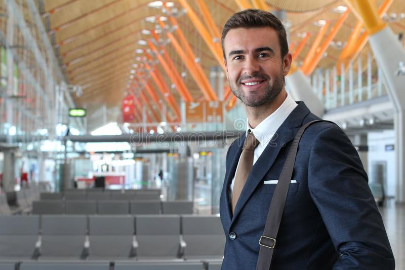 Handsome businessman smiling at the airport with space for copy stock image