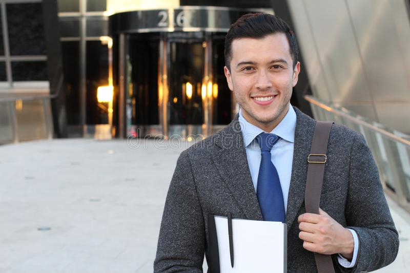 Handsome businessman smiling outside the office building stock photo