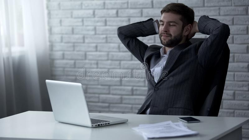 Handsome businessman smiling after successful online deal, lucrative contract. Stock photo royalty free stock photo