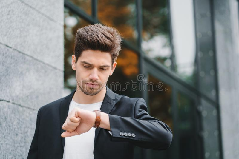 Handsome businessman or student looks at watch. Young man in hurry late for work. Male model on office building stock photos