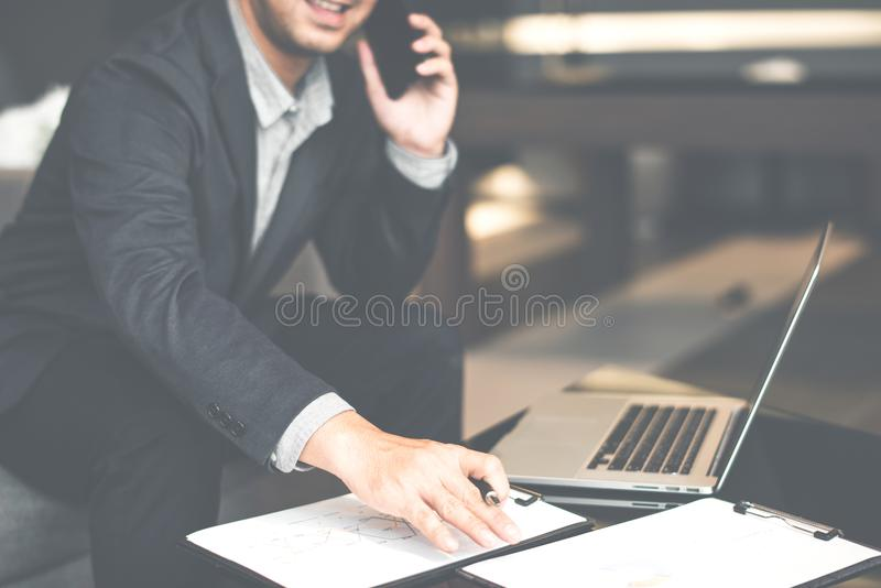 Handsome businessman in suit and eyeglasses speaking on the phone in office,Side view shot of a man`s hands using smart phone in r royalty free stock photography