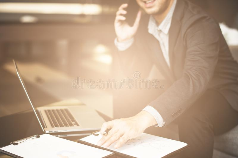 Handsome businessman in suit and eyeglasses speaking on the phone in office,Side view shot of a man`s hands using smart phone in r royalty free stock images