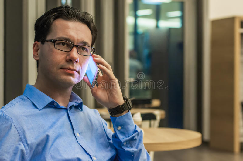 Handsome businessman talking on the phone in a cafe.  royalty free stock photography