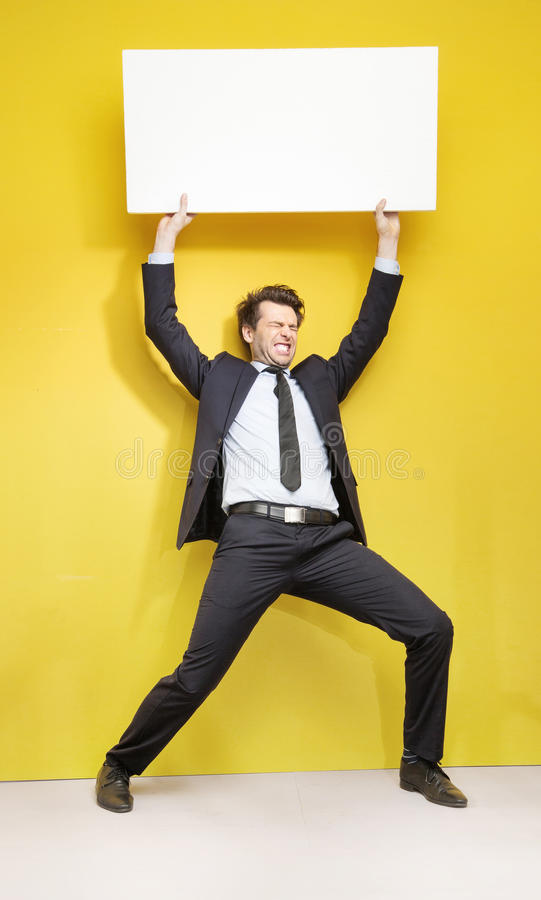 Handsome businessman trying to lift up the board royalty free stock photos