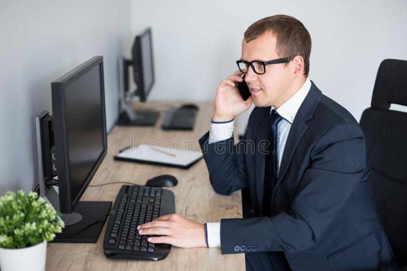 Handsome businessman using computer and talking by phone in office royalty free stock photo