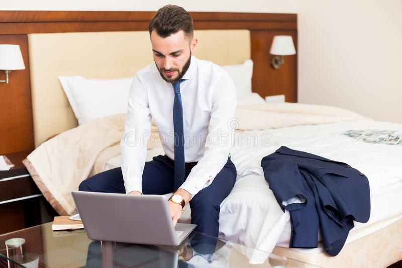 Handsome Businessman Using Laptop in Hotel Room royalty free stock image