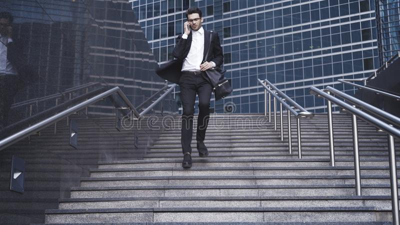 A handsome businessman walking down stairs and having phone conversation. stock image