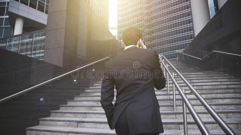 A handsome businessman walking up stairs and having phone conversation. stock image