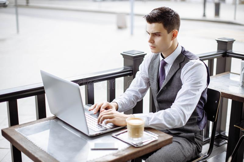 Handsome businessman wearing suit and using modern laptop outdoors, successful manager working in cafe during break and searching stock image