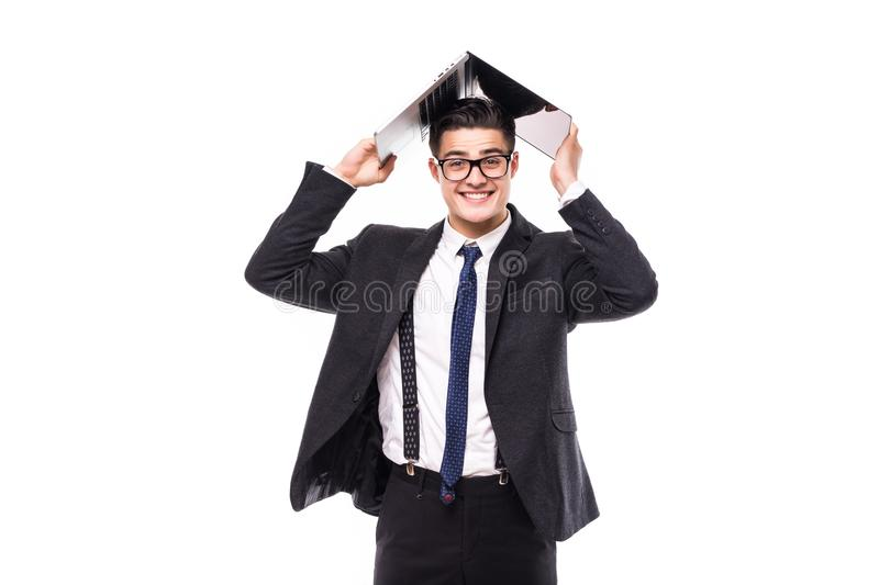 Handsome businessman which holds a laptop above his head in formals standing isolated over white background stock image