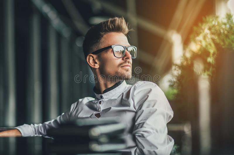 Handsome businessman in white shirt sitting at table in cafe and looking away. Sunlight background royalty free stock photography