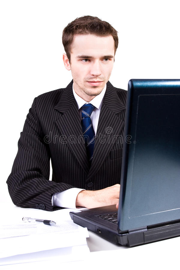 Handsome businessman at work writing on computer stock images