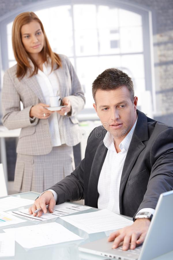 Handsome businessman working at desk stock photography