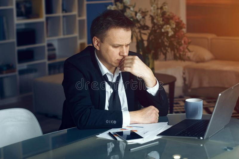 Handsome businessman working from home. Businessman in black suit working at home. Sitting at table and reading information on laptop stock photography