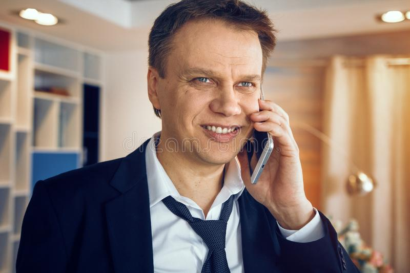 Handsome businessman working from home. Standing middle room and speaking over phone royalty free stock images