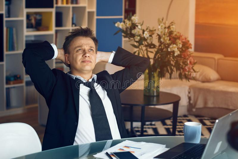 Handsome businessman working from home. Thoughtful businessman sitting at table and thinking about new business ideas. Business at home concept royalty free stock photo
