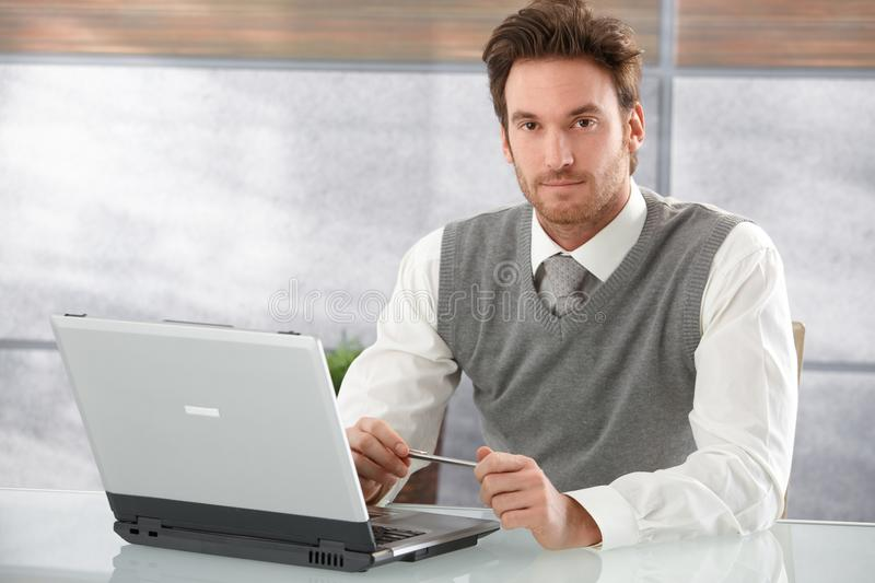 Handsome businessman working on laptop stock photography