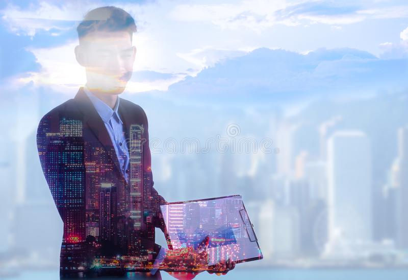 Handsome businessperson using laptop on abstract city and sky background with copy space. Communication concept stock images