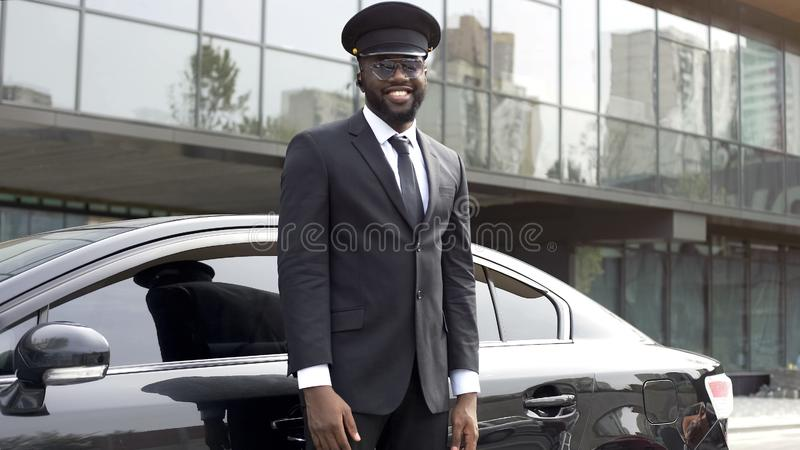 Handsome cabdriver sincerely smiling near his luxury vehicle, elite service. Stock photo royalty free stock photography