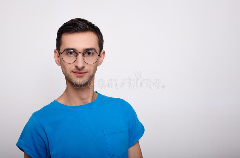 Portrait of a serious young man with glasses and a blue T-shirt on a white background. A handsome, calm confident young man with dark hair and in round glasses stock photos