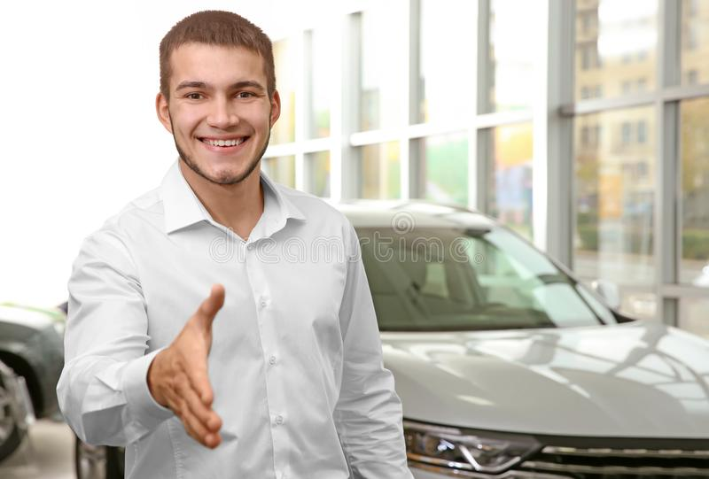 Handsome car salesman reaching out for handshake. In dealership centre royalty free stock images