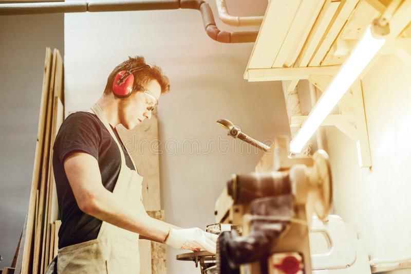 Handsome carpenter using table jigsaw royalty free stock photos