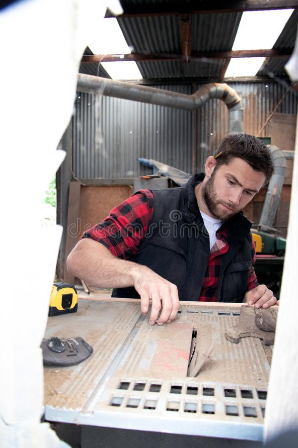 Carpenter, wood worker work measuring, drilling and making timber product royalty free stock image