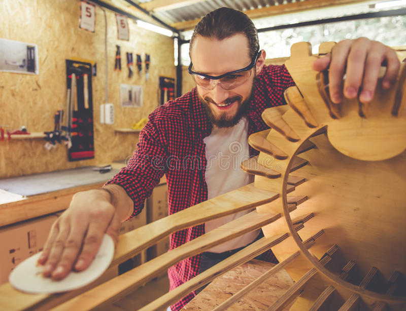 Handsome carpenter working. Handsome carpenter in protective glasses is smiling while working with wood and sandpaper in the workshop royalty free stock images